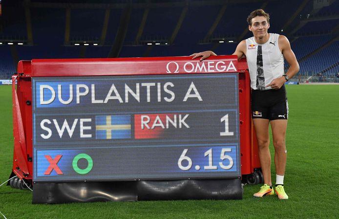 Armand Duplantis poserend bij het bord dat z'n wereldrecord aangeeft.