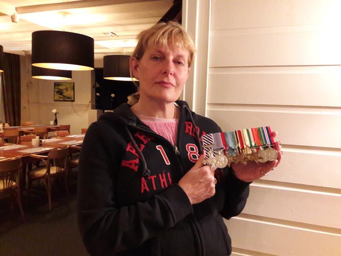 Eugenie Brooks, dochter van Engelse piloot, laat de medailles zien die zij nog in bezit heeeft. De ID-kaart van haar vader werd wel gestolen.