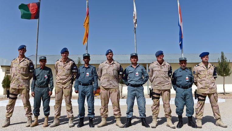 Nederlandse soldaten met Afghaanse politieagenten in Kunduz in 2013. Beeld AFP