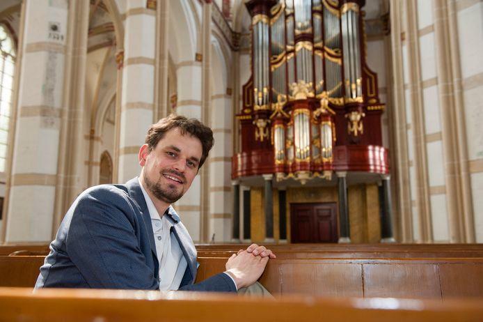 Organist Hugo Bakker met op de achtergrond het monumentale orgel van de Sint-Maartenskerk in Zaltbommel.