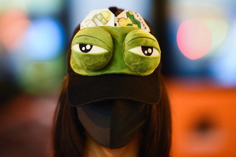 Een demonstrant in Hongkong draagt Pepe the Frog op haar pet. De demonstranten gebruiken de kikker als symbool voor hun verzet tegen meer invloed van China op Hongkong. In de VS is de kikker juist een symbool voor de extreem- rechtsealt-rightbeweging.  Beeld AFP