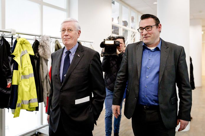 VVD-prominent Hans Wiegel loopt aan de zijde van verkiezingswinnaar Richard de Mos de Haagse raadzaal binnen.