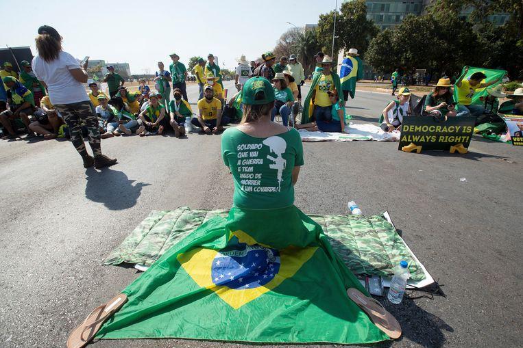 Een groep vrachtwagenchauffeurs blokkeert de wegen van de 'Esplanade of Ministries' in Brasília, om president Bolsonaro te steunen. Beeld EPA