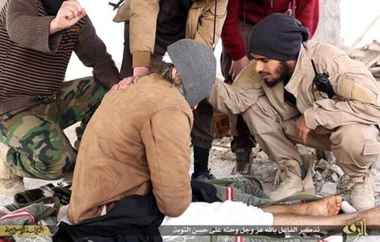 Een extremist met walkie talkie checkt de toestand van het gewonde slachtoffer alvorens de man wordt gestenigd.