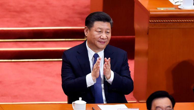 Partijleider Xi Jinping applaudisseert na de uitslag van een stemming op het partijcongres. Beeld null