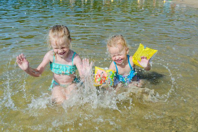 Fenna en Sophie zoeken verkoeling in het water van het Henschotermeer dat duizenden bezoekers trok.