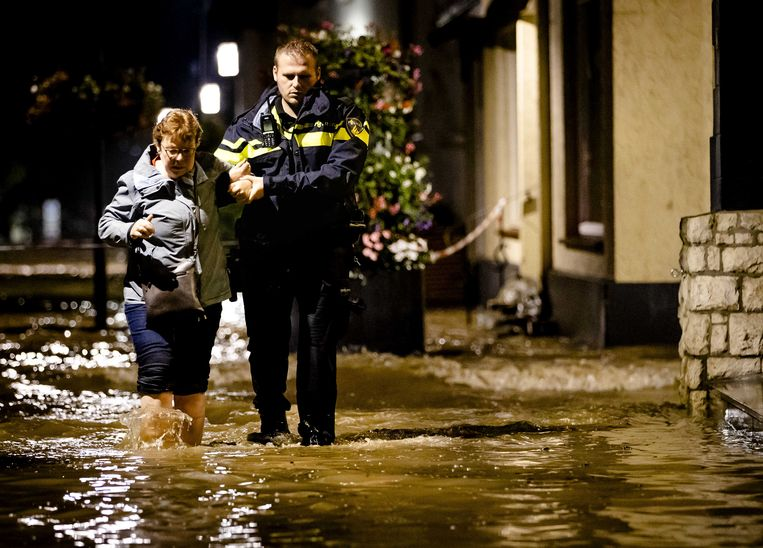 Een politieagent evacueert een bewoner. Door het almaar stijgende hoge water als gevolg van de de overstroming van de Geul zijn de straten in Valkenburg ondergelopen.  Beeld ANP