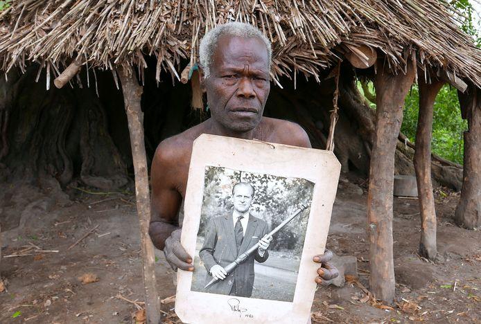 Een bewoner van Tanna toont de foto van prins Philip waar hij poseert met de houten stok die de dorpelingen voor hem maakten. (foto uit 2017)