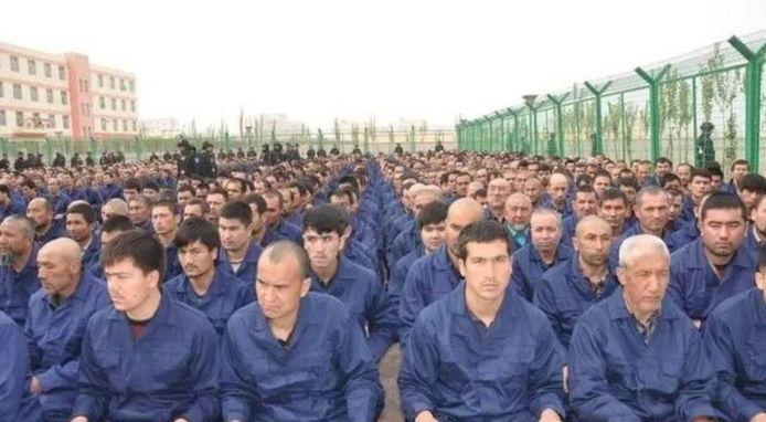 Beeld van mannelijke Oeigoerse gevangenen in een heropvoedingskamp.