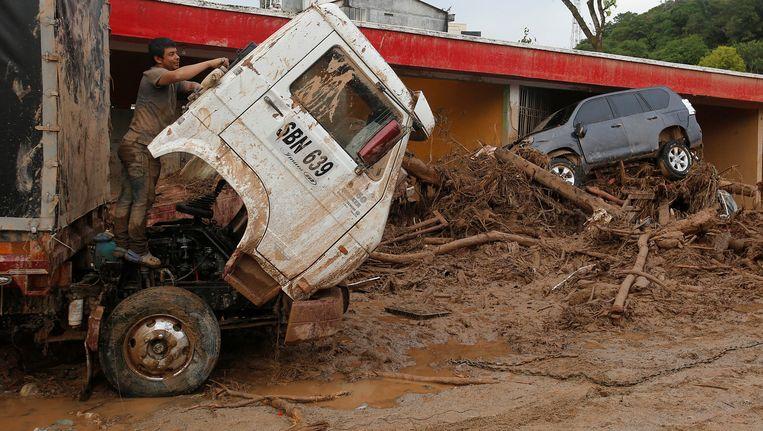 Een man klimt op een truck in een overspoeld Mocoa. Beeld REUTERS
