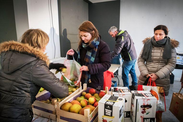 ► Mensen kopen lokale producten allerlei, zoals fruit, bij de buurderij in Meise. Alleen is 'lokaal' relatief, zo blijkt. Beeld Tim Dirven