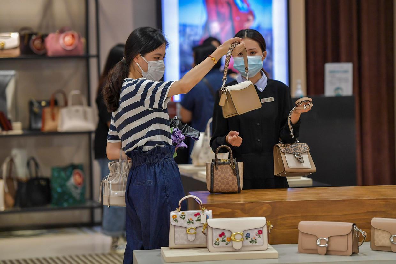 Een Chinese toerist koopt een handtas in Haikou. Beeld China News Service via Getty Ima