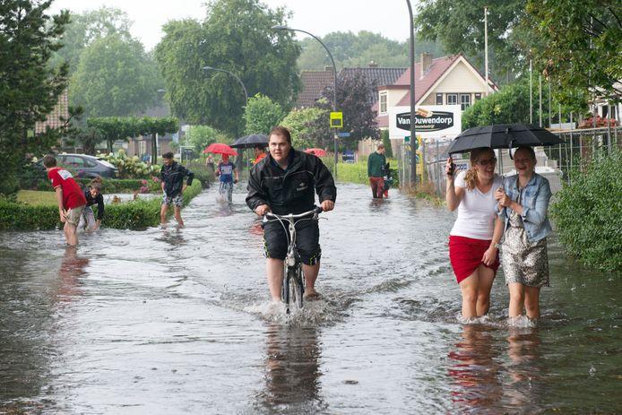 De hoofdstraat van Elspeet op de Veluwe staat volledig blank na een zomerse hoosbui. Volgens klimaatwetenschappers gaan we dit soort taferelen vaker zien.