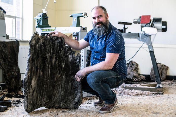 Houtbewerker Peter Peer uit Velp (bij Grave) toont een stuk van een middeleeuwse uitgeholde boomstam, die deel uitmaakte van de waterput die in Wijchen werd gevonden.
