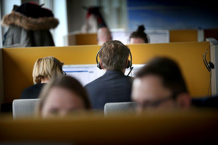 Minister Sander Dekker (Rechtsbescherming) luistert mee in het callcenter tijdens een werkbezoek in Leeuwarden. Beeld Hollandse Hoogte /  ANP