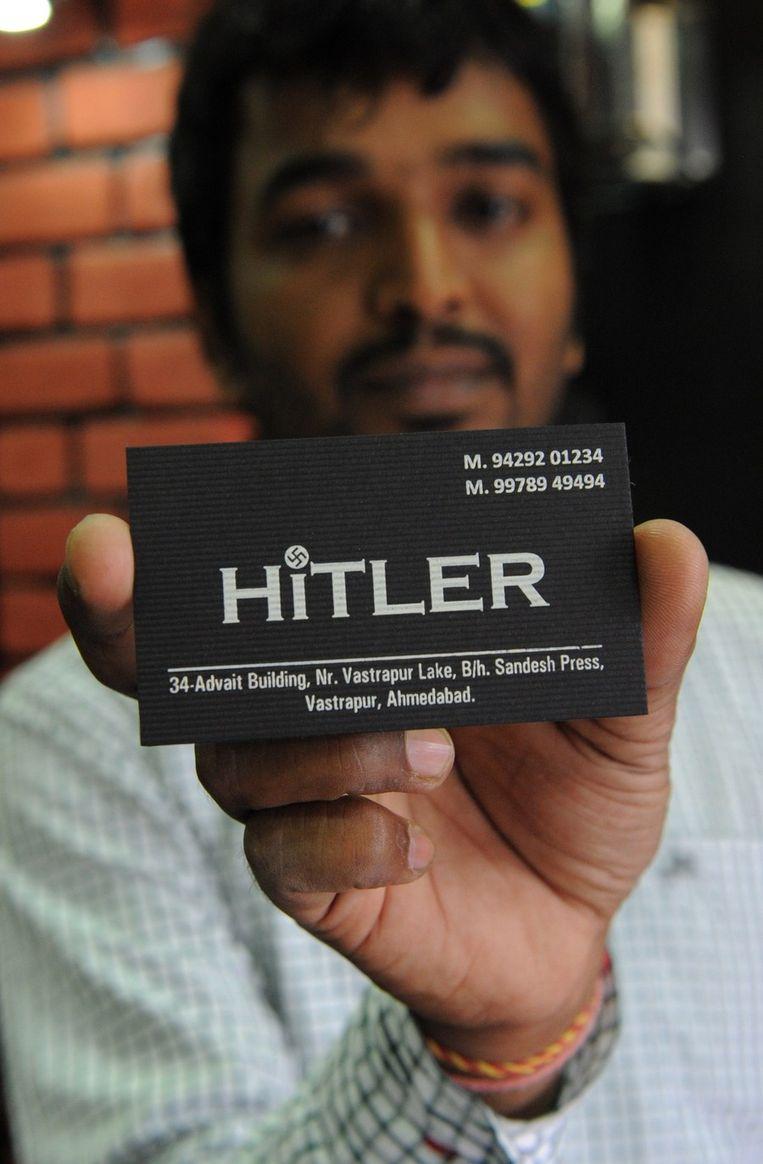 Rajesh Shah met een visitekaartje van zijn winkel Beeld afp