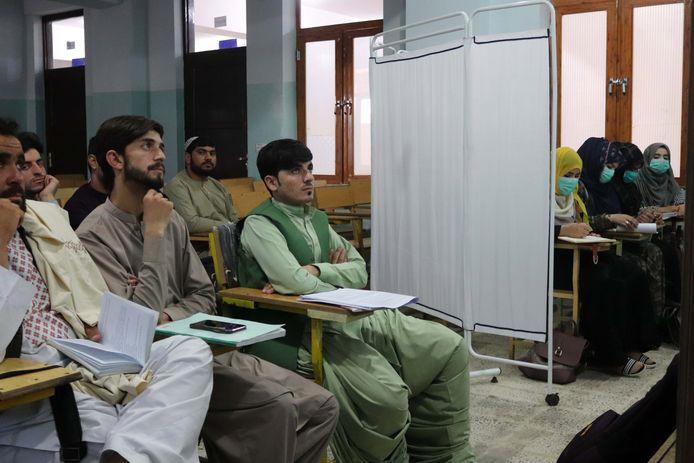 Des étudiants afghans séparés par une cloison assistent à un cours à l'université Mirwais Neeka de Kandahar, en Afghanistan, le 20 septembre 2021. Les talibans ont officiellement annoncé le 12 septembre une ségrégation des étudiants masculins et féminins dans toutes les universités gouvernementales et privées du pays.
