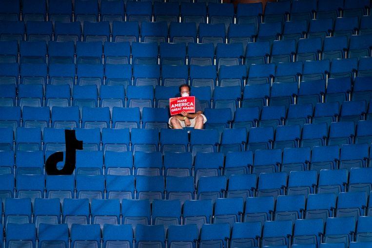 Een eenzame Trumpsupporter in Tulsa. K-popfans hadden kaarten gereserveerd en kwamen daarna niet opdagen, hierdoor zat de arena maar halfvol. Beeld Getty Images, illustratie: Studio V