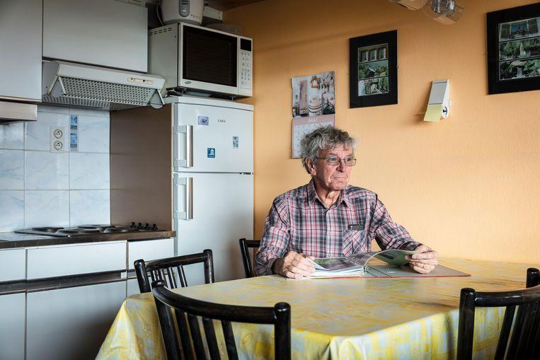 Jean-Marc aan tafel met een boek vol herinneringen. Beeld Piet Goethals