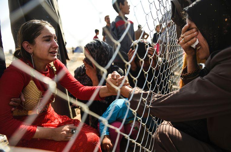 Irakezen die in 2016 zijn gevlucht uit de Iraakse stad Mosul, die toen onder controle was van IS, huilen bij het weerzien van familieleden in het Koerdische vluchtelingenkamp in Aksi Kalak, 40 kilometer ten oosten van de Koerdische stad Erbil.  Beeld AFP