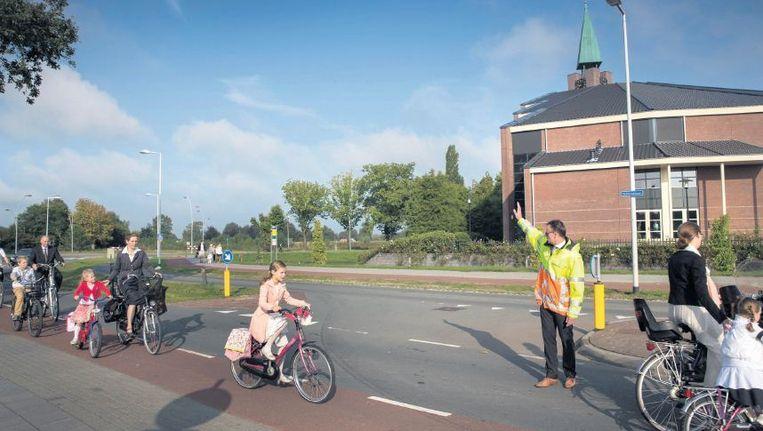 Op weg naar een kerkdienst in de Hoeksteen in Barneveld. De toeloop naar de 'refodome' - de kerk heeft 3500 leden - is zo groot dat er verkeersregelaars worden ingezet. Beeld Werry Crone