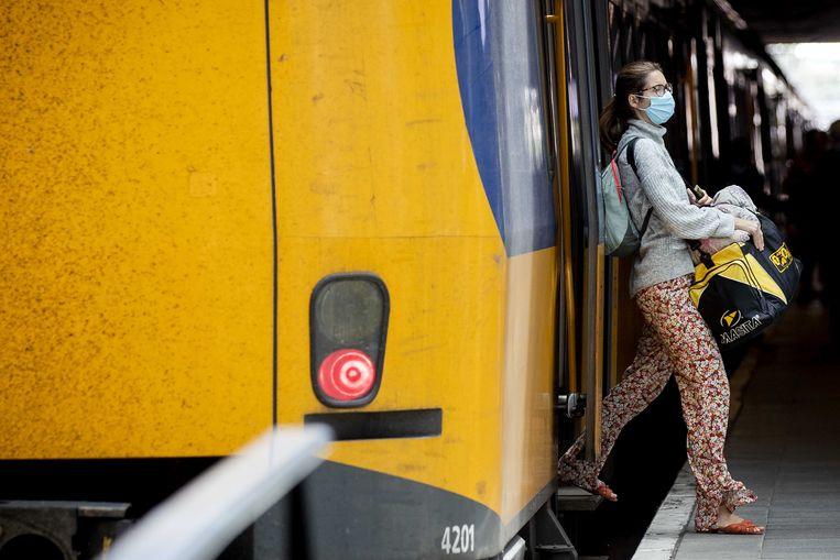 Een reiziger met een mondkapje stapt op Den Haag Centraal uit de trein.  Beeld ANP