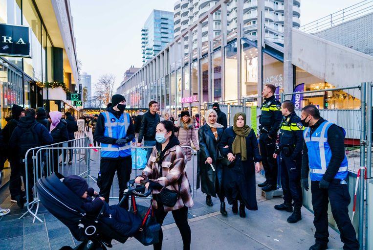 Beveiligers wijzen mensen op het eenrichtingsverkeer op de Lijnbaan tegen het einde van een drukke koopzondag in het centrum van Rotterdam.  Beeld ANP