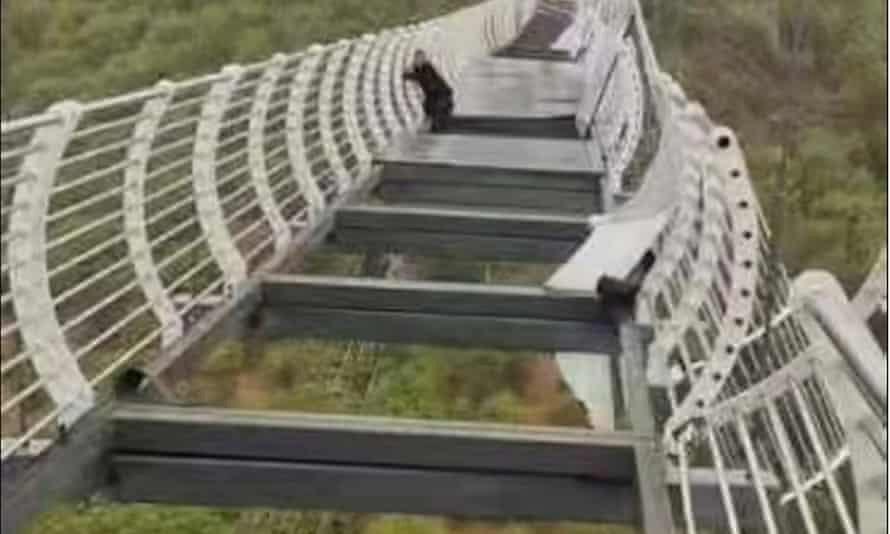 Chinese toerist houdt zich stevig vast aan de brug nadat de glazen panelen zijn neergestort.