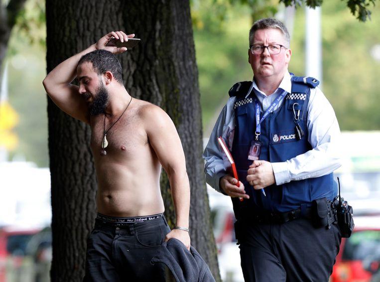 Een politieagent begeleidt een man weg van de moskee. Beeld AP