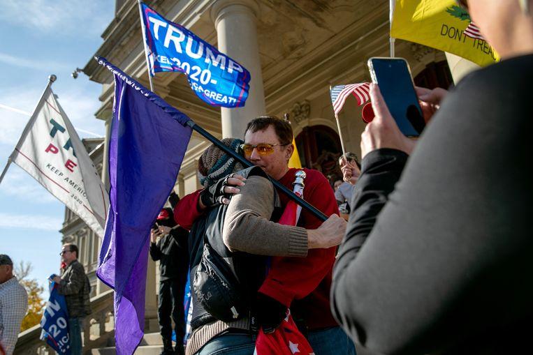 Een Trump-aanhanger en een Biden-aanhanger omhelzen elkaar in Lansing, Michigan, tijdens een demonstratie tegen de winst van Biden.  Beeld Getty Images