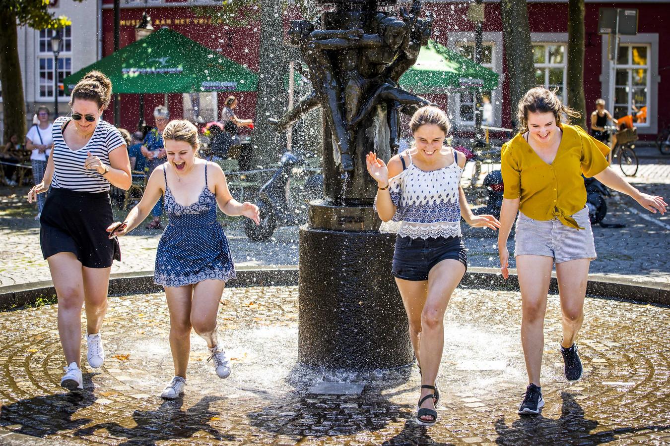 Met temperaturen boven de dertig graden zoeken mensen verkoeling bij de fontein in Maastricht.
