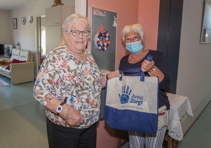 Rie Goedegebuure krijgt een verrassingstasje aangeboden van zorgcoöperatie Anna Zorgt. Rechts vrijwilliger en bestuurslid Ine van Ommen.
