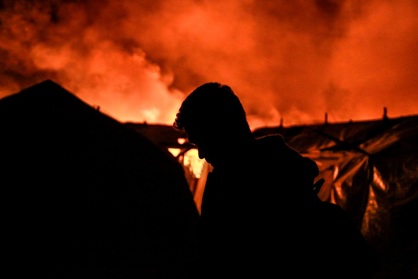 Een migrant staat naast een tent, terwijl op de achtergrond de vlammen en rook de lucht vullen.