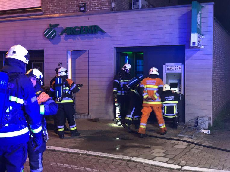 De brandweer meet de schade op aan de bankautomaat