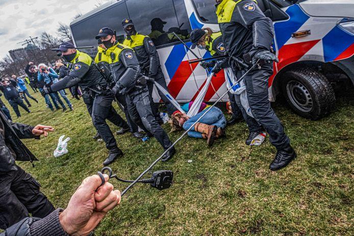 Een demonstrant pakt de portofoon van een agent.