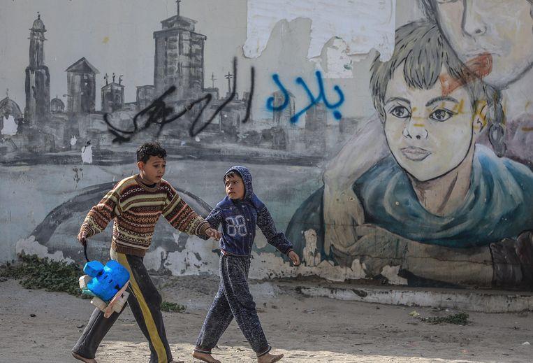 Palestijnse jongens lopen op straat in het vluchtelingenkamp al-Shatea in de Gazastrook.  Beeld EPA