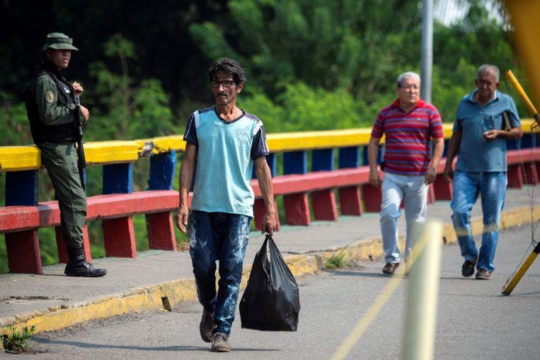 Een soldaat van de nationale garde houdt de wacht bij een brug aan de grens tussen Venezuela en Colombia.  Beeld AFP