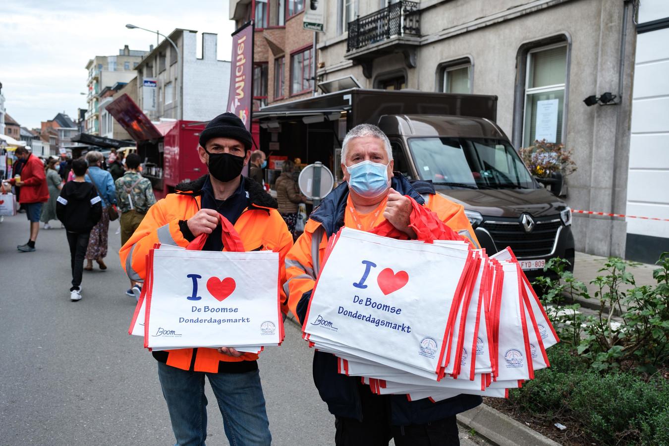 Stewards Hugo Hellemans en Francois De Beyn delen gratis shoppingtassen uit.