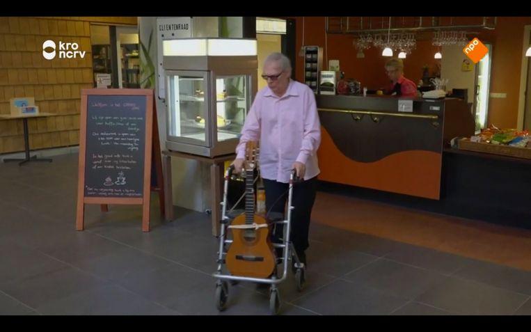 Oscar Benton heeft zijn gitaar met een elastiekje aan zijn rollator vastgebonden. Beeld NPO/KRO-NCRV