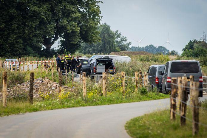 De politie doet onderzoek naar het gevonden lichaam in de Waal bij Deest.