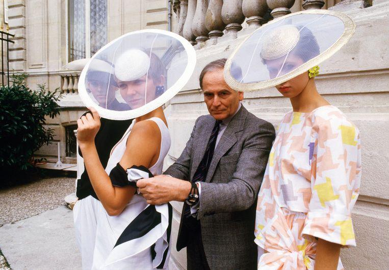 Pierre Cardin in 1984 geflankeerd door twee modellen gekleed in zijn creaties uit de 'ready-to-wear'-zomercollectie. Beeld AP