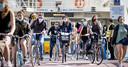 Reizigers met mondkapjes bij de pont achter Amsterdam CS. Dankzij corona floreert de fiets, met name de e-bike