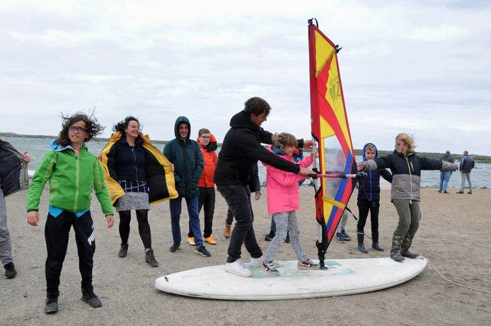 Engels docente Winny de Ruiter (in gele jas) en surfleraar Dani van Crasbeek (op de plank) met hun leerlingen. Het meisje in de roze jas is Solveig Dornig. Ze is de jongste deelnemer