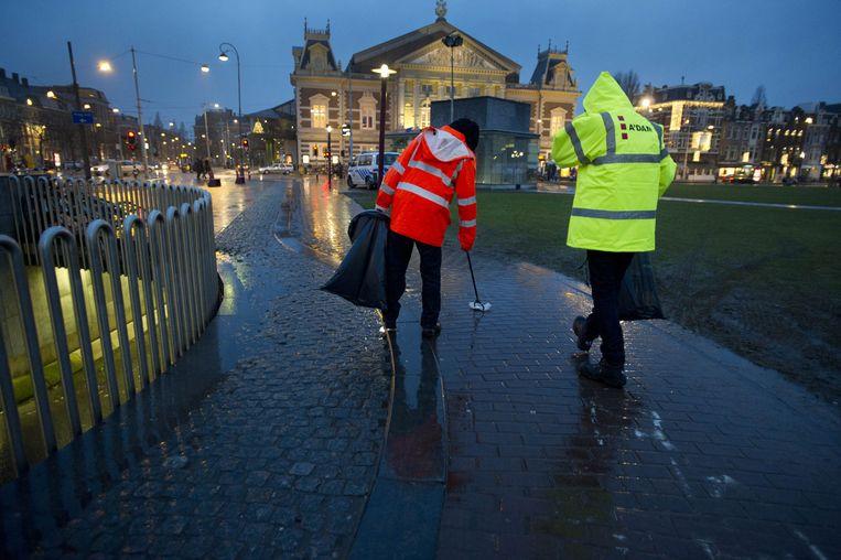 Een taakstraf in uitvoering op het Museumplein in Amsterdam. Beeld ANP