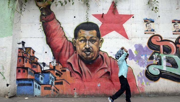 Een man loopt langs een muurschildering van president Hugo Chávez in Caracas, op 1 januari. Beeld AFP
