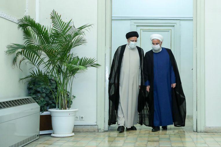 Scheidend president Hassan Rohani wandelt met de aankomende president Raisi naar buiten na een ontmoeting in Teheran. Beeld AP