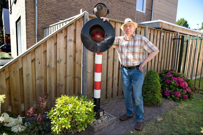 Bestenaar Hans Vervoort met de oude signaalpaal die nu bij hem in de tuin staat.