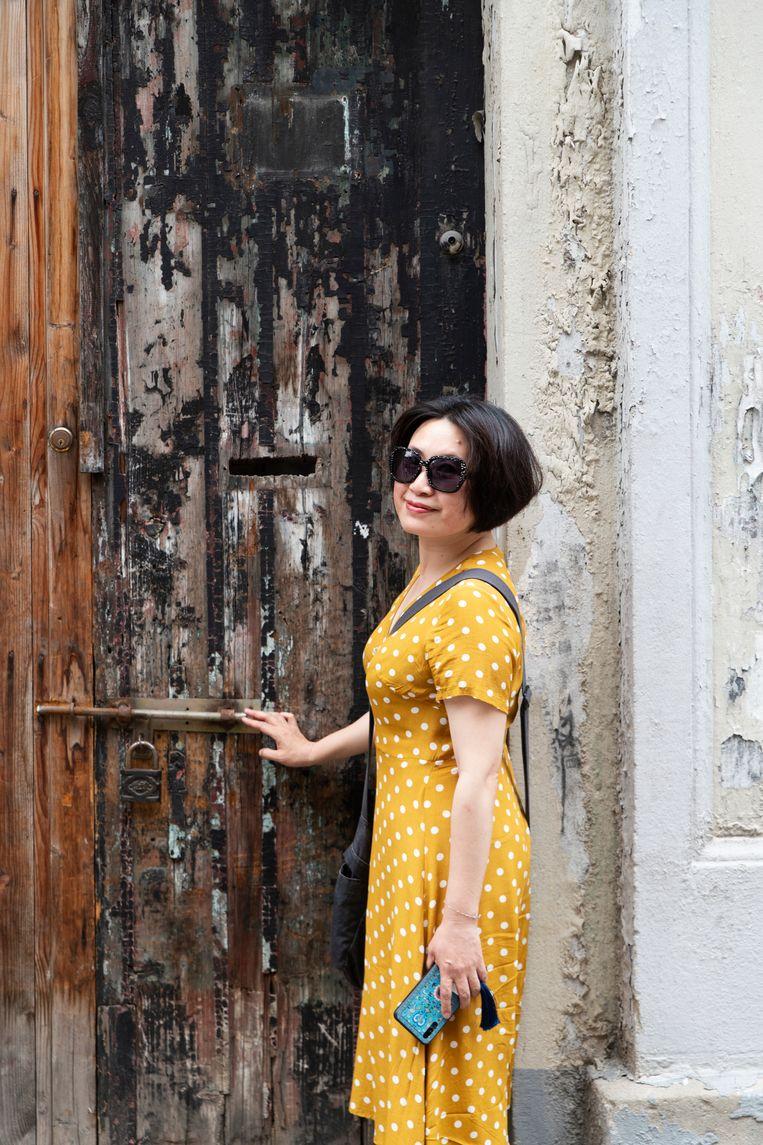 Xiao Hong poseert voor de verveloze deur van haar ouderlijk huis.  Beeld Matjaz Tancic