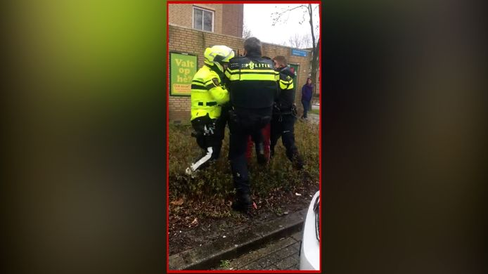 Een agent deelt een knietje uit aan de woedende vader van een baby die door andere agenten wordt vastgehouden.