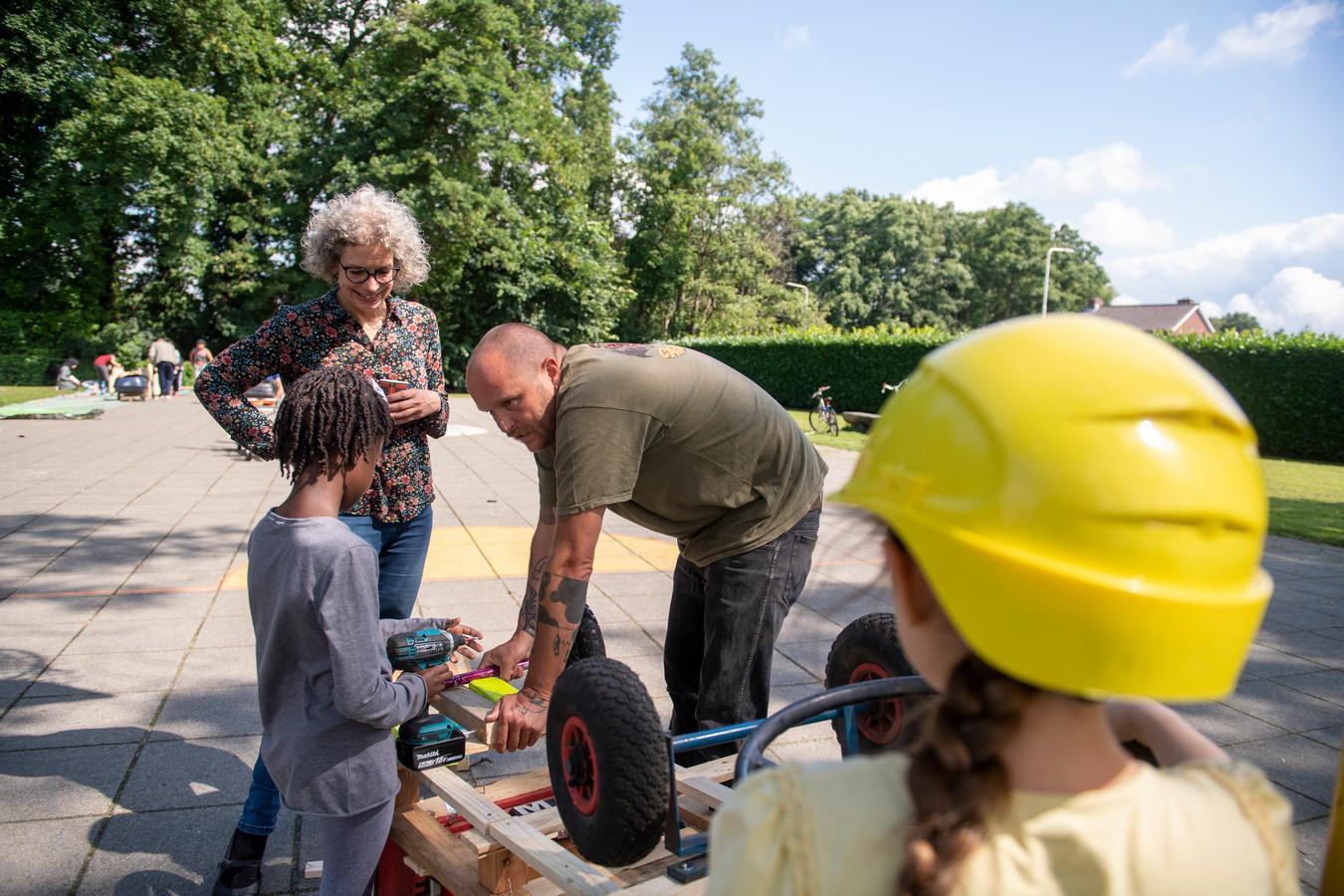 Gertie en Chris van De Vrolijkheid helpen Amira en Leen (met helm) bij het bouwen van hun zeepkist.